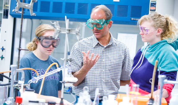Professor instructs two students in lab session